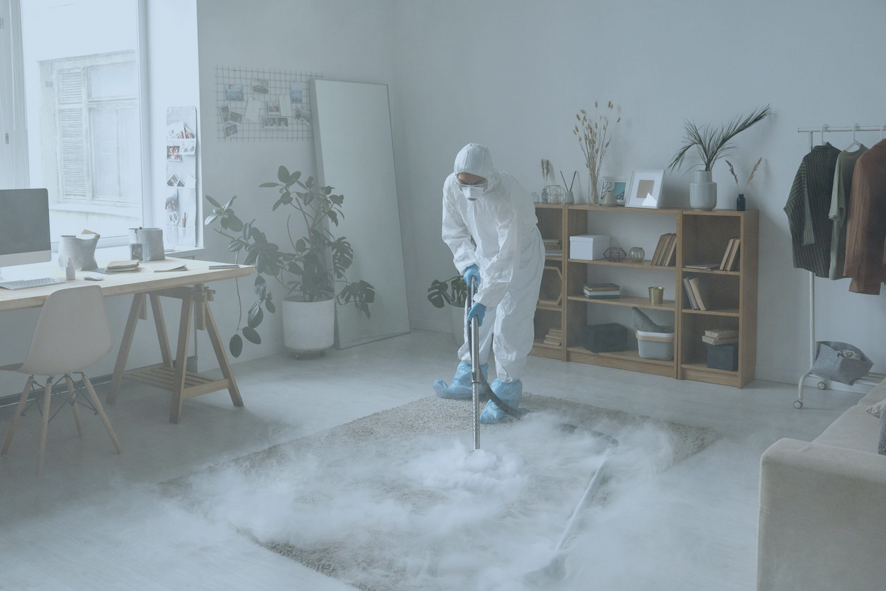 Woman in PPE cleaning a carpet with a chemical spray