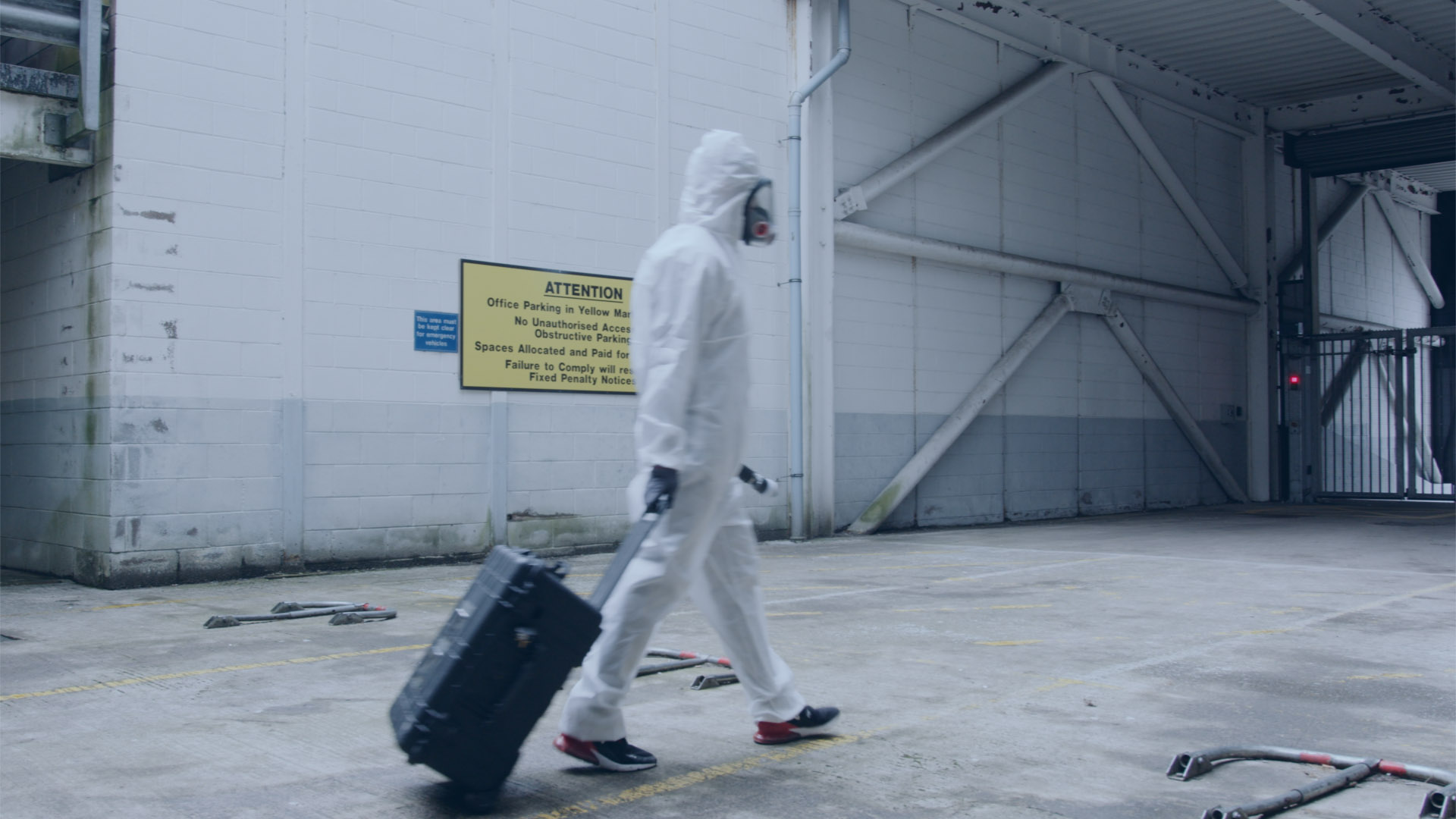 Man in hazmat suit walking through an industrial building