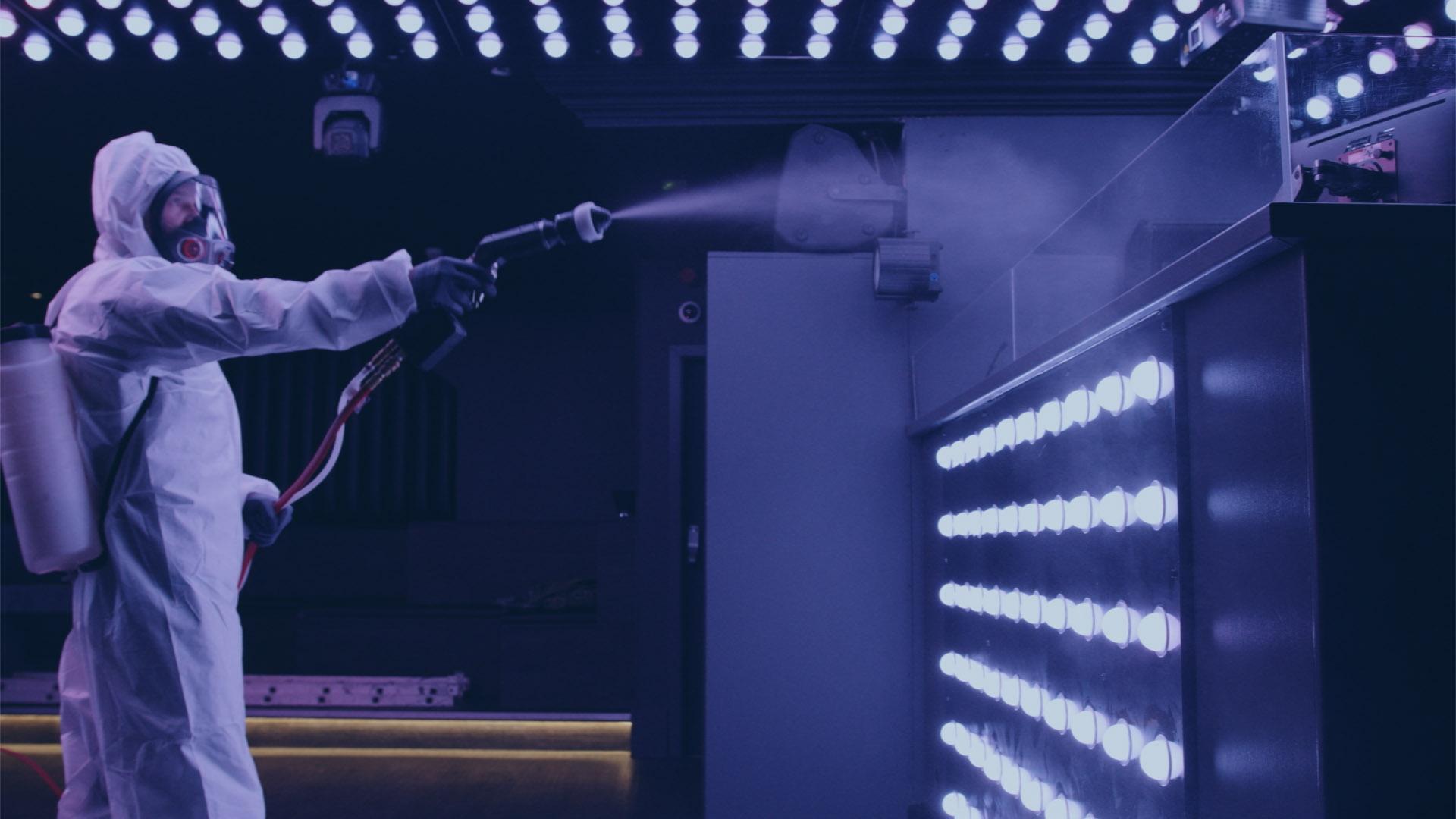 Man in hazmat suit spraying a night club wall